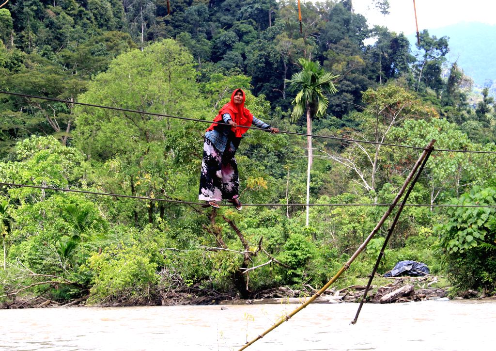 ACEH, Feb. 2, 2019 - A woman holds wires to cross a river at Sikundo village in West Aceh, Indonesia, Feb. 2, 2019. Locals have to cross the river with the help of wires as there is no proper bridge ...