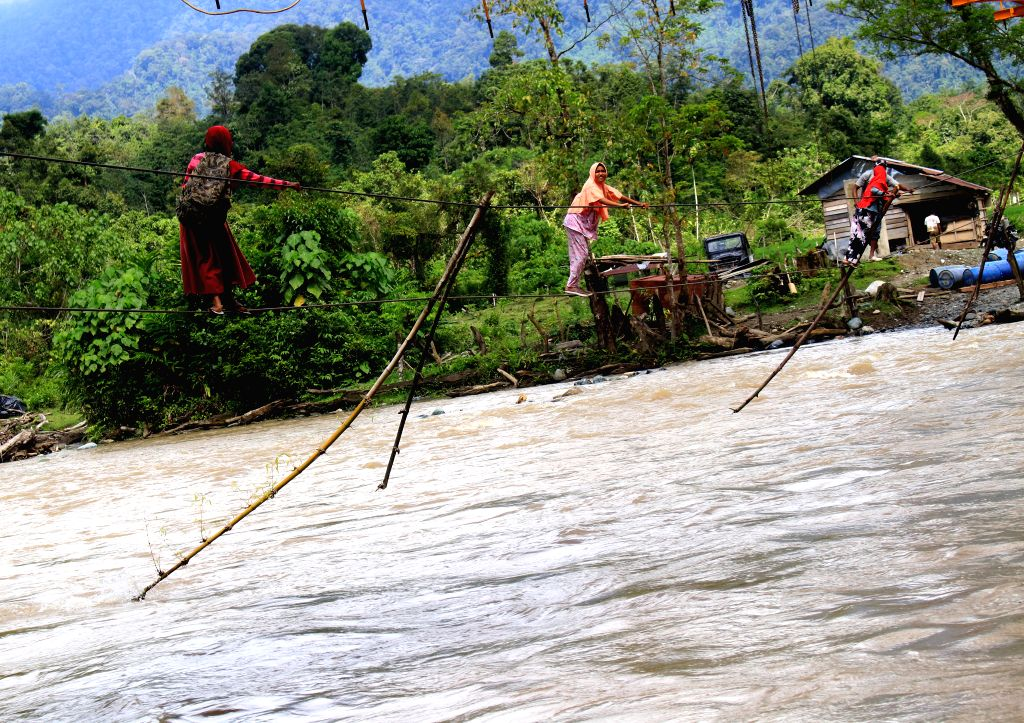 ACEH, Feb. 2, 2019 - Residents hold wires to cross a river at Sikundo village in West Aceh, Indonesia, Feb. 2, 2019. Locals have to cross the river with the help of wires as there is no proper bridge ...