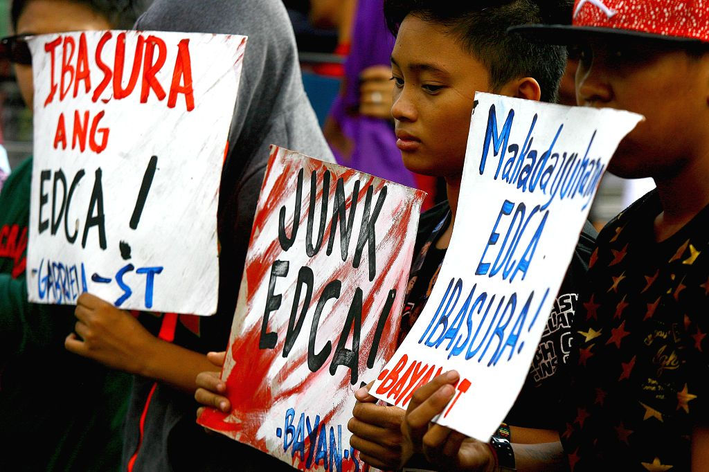 Activists hold placards during a protest rally in front of the U.S. Embassy in Manila, the Philippines, Jan. 14, 2016. The activists are calling for an end to the ...