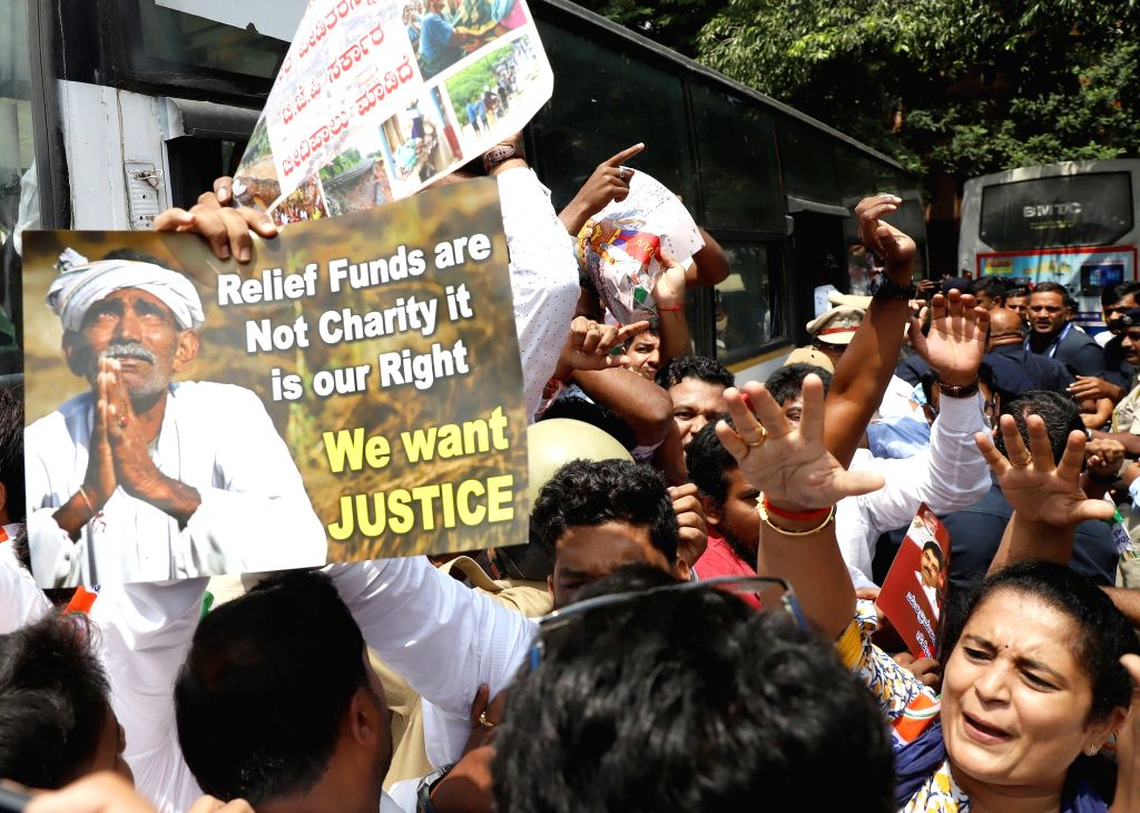 Activists of Karnataka Youth Congress stage a demonstration against the Central and State Government over inadequate relief funds for the state's flood victims, in Bengaluru on Oct 12, ...