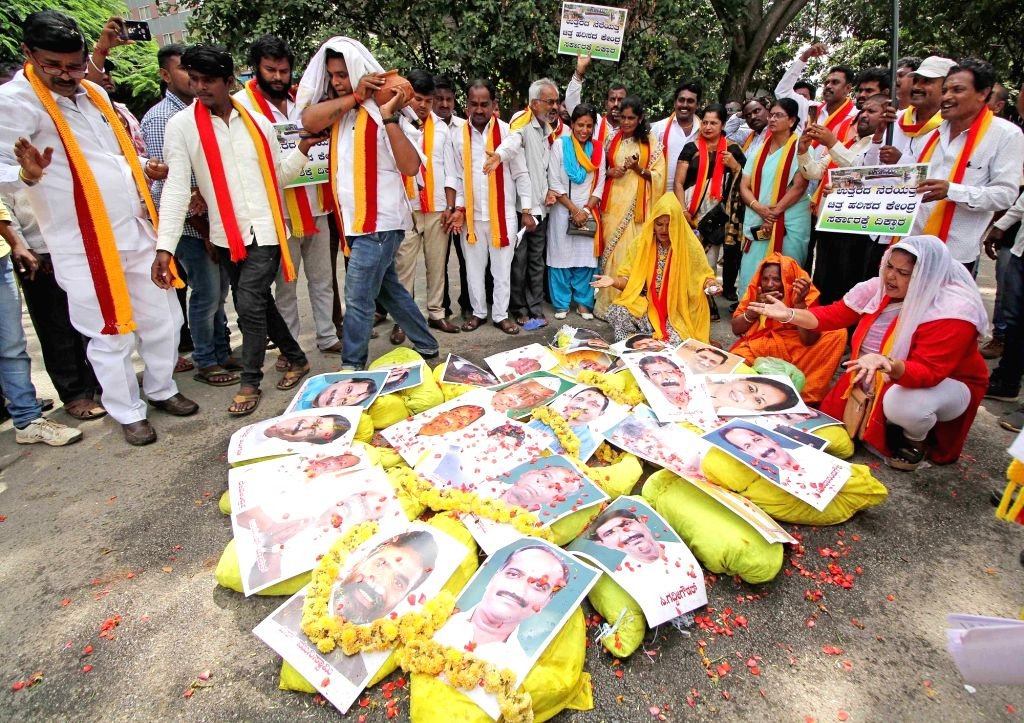 Activists of Kasturi Karnataka Janapara Vedike (KKJV) burn the photos of Karnataka BJP MPs as they protest against the Central and the State Government over their alleged failure to ...