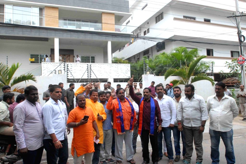 Activists of Vishwa Hindu Parishad (VHP) stage a demonstration outside the residence of religious leader Swami Paripoornananda after the police placed him under house arrest, in Hyderabad ...