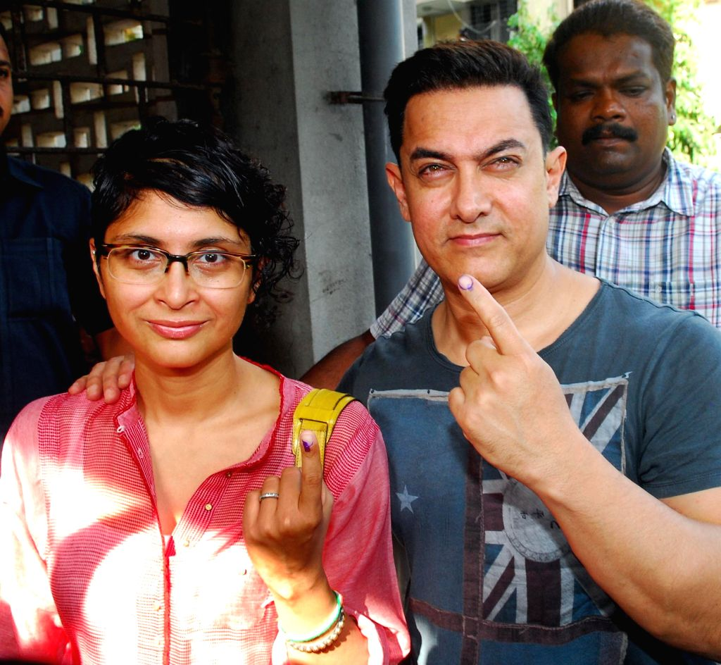 Actor Aamir Khan and his wife filmmaker Kiran Rao show their fore fingers marked with phosphorous ink after casting their votes at a polling booth during the sixth phase of 2014 Lok Sabha Polls in ...