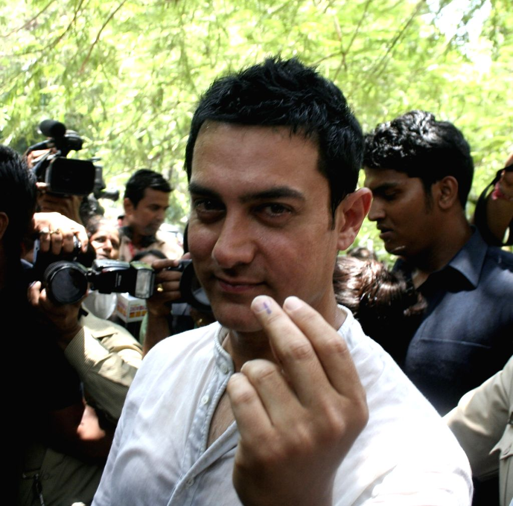 Actor Aamir Khan shows his finger after casting his vote in Mumbai.