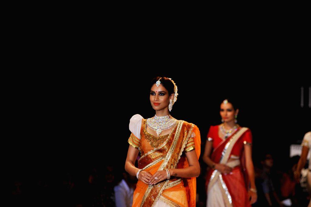 Actor Amrita Patki walks on the ramp showcase the jewellery by Indian Institute of Gems and Jewellery (IIGJ) during the India International Jewellery Week (IIJW) in Mumbai, on July 14, 2014. - Amrita Patki
