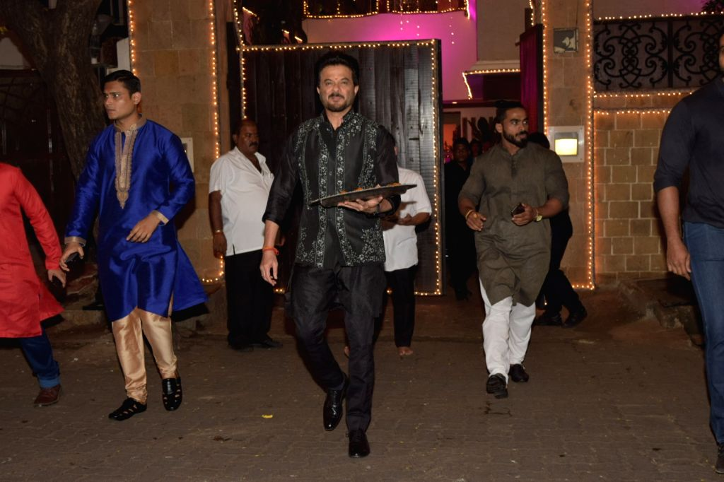 Actor Anil Kapoor distributes sweets among media personnel at his Diwali bash in Mumbai on Oct 27, 2019. - Anil Kapoor