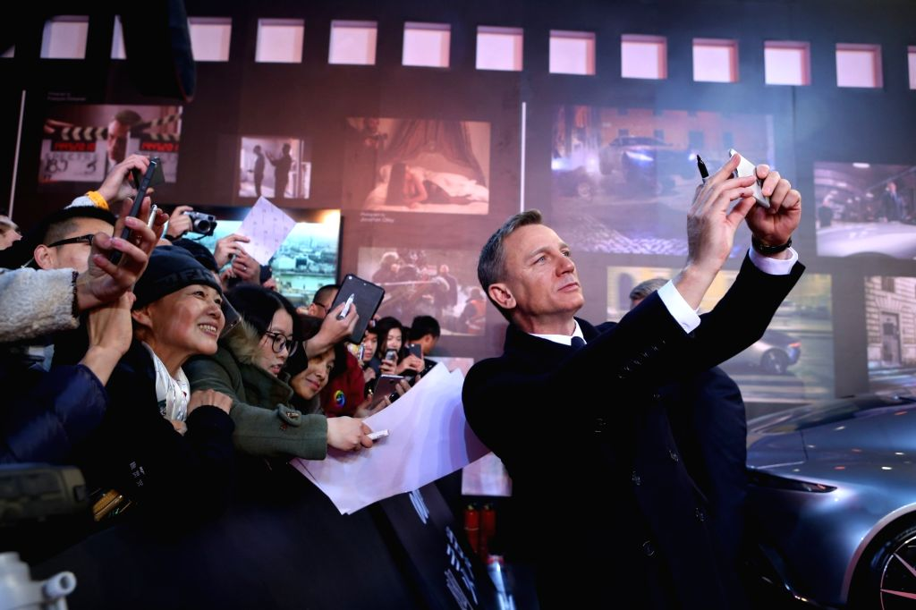 Actor Daniel Craig poses for photos with fans during the red carpet of the movie `Spectre` of the James Bond saga in Beijing on Nov. 12, 2015. - Daniel Craig