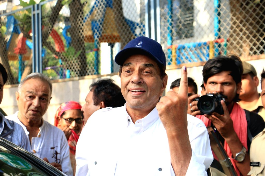 Actor Dharmendra show their forefingers marked with indelible ink after casting vote during the fourth phase of 2019 Lok Sabha elections in Mumbai on April 29, 2019. - Dharmendra