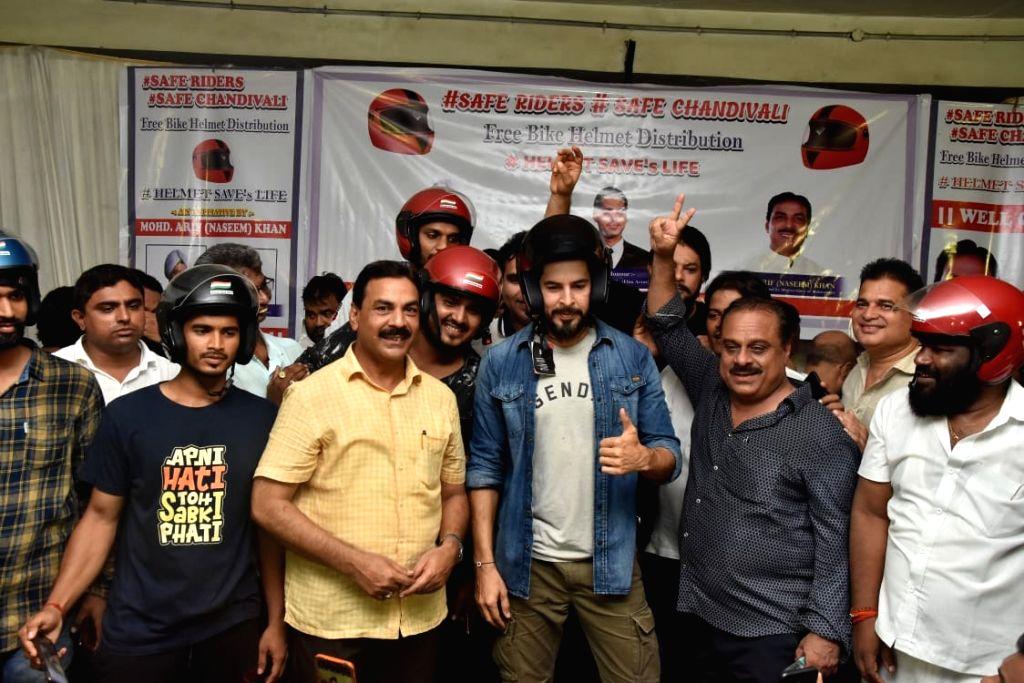 Actor Dino Morea and Congress MLA Naseem Khan during a 'Free Bike Helmet Distribution' programme in Mumbai on Sep 8, 2019. - Dino Morea and Naseem Khan