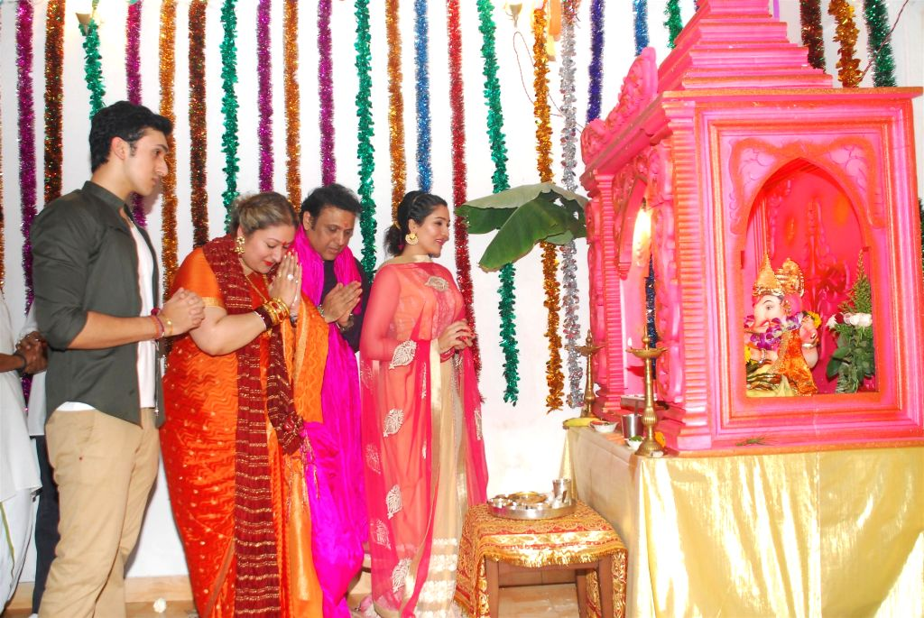 Actor Govinda with his wife Sunita and son Yashowardan daughter Narmada during the Ganesh Chaturthi celebrations at his residence in Mumbai on Aug 29, 2014.