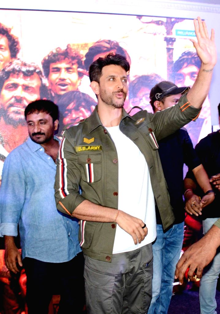 """Actor Hrithik Roshan accompanied by mathematician Anand Kumar, waves at a fan during the promotions of his film """"Super 30"""" in Patna on July 16, 2019. - Hrithik Roshan and Anand Kumar"""