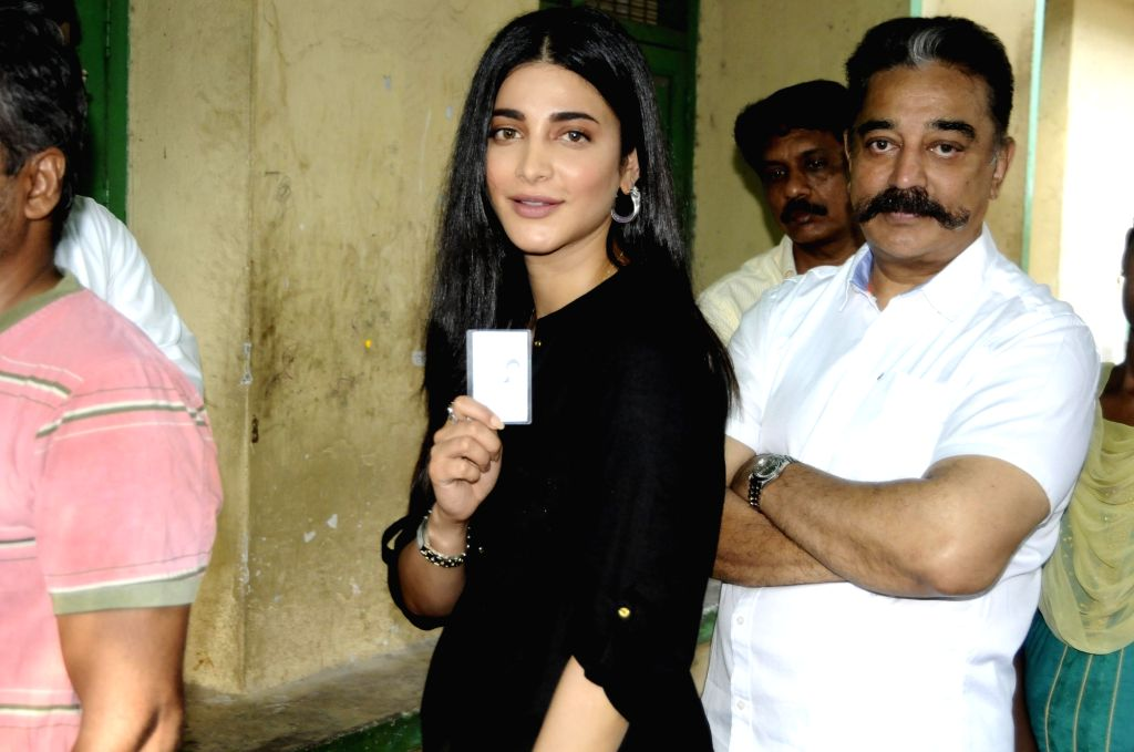 Actor Kamal Haasan with her daughter-actress Shruti Haasan wait in a queue to cast vote during the second phase of the 2019 Lok Sabha polls, in Chennai, on April 18, 2019. - Kamal Haasan