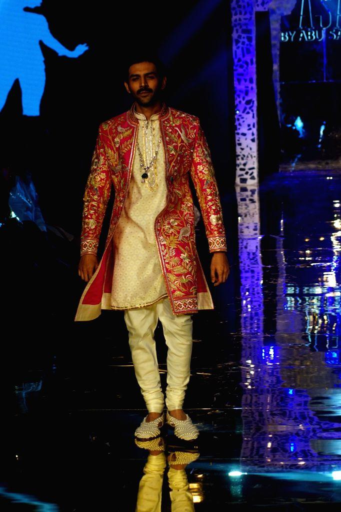 Actor Kartik Aaryan walks the ramp showcasing creations of fahoion designers Abu Jani and Sandeep Khosla in Mumbai on Oct 16, 2019. - Kartik Aaryan