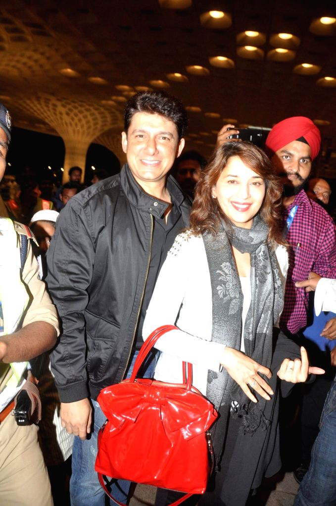 Actor Madhuri Dixit along with her husband Dr Shriram Nene at the Terminal 2 of the Chhatrapati Shivaji International Airport, in Mumbai, on April 23, 2014. The Bollywood actor left to attend the ... - Madhuri Dixit