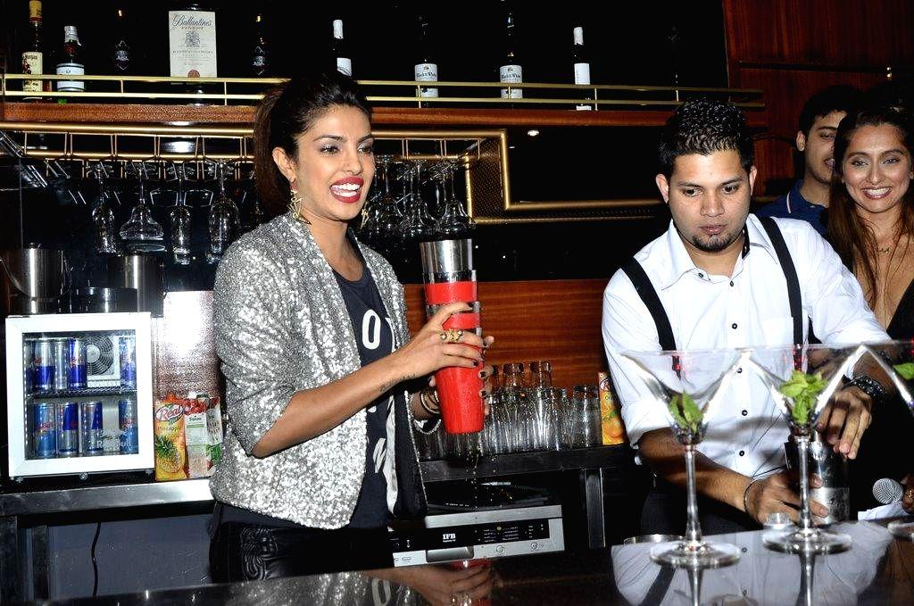 Actor Priyanka Chopra prepares a cocktail at the bar after launching her brother Siddharth Chopra's pub-lounge entitled Mugshot Lounge, in Pune on Sept 7, 2014. - Siddharth Chopra