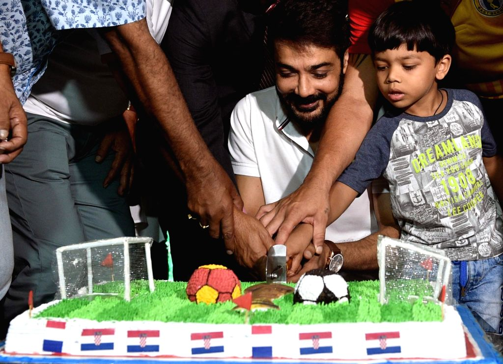 Actor Prosenjit Chatterjee cuts a cake along with with football enthusiasts as they cheer ahead of FIFA World Cup 2018 final match between France and Croatia, in Kolkata on July 15, 2018. - Prosenjit Chatterjee