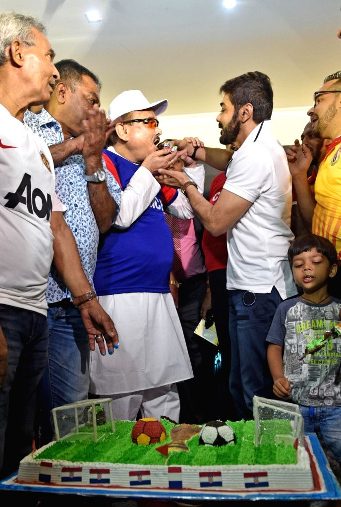 Actor Prosenjit Chatterjee fetches a piece of cake to TMC leader Madan Mitra as they cheer ahead of FIFA World Cup 2018 final match between France and Croatia, in Kolkata on July 15, 2018. - Prosenjit Chatterjee