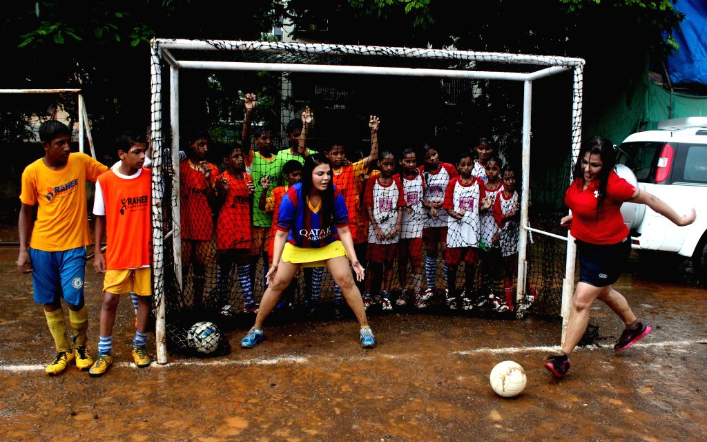 Actor Rakhi Sawant and Brazilian singer Carlyta Mouhini play football with students to create awareness of football, in Mumbai on July 10, 2014.
