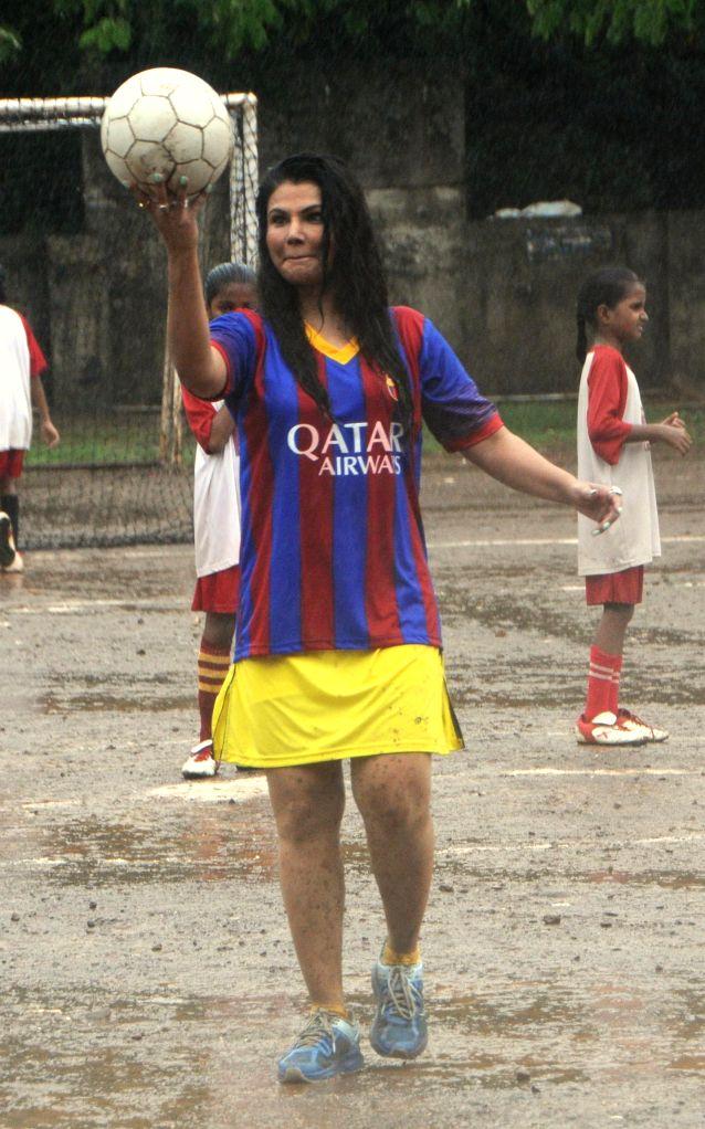 Actor Rakhi Sawant play football with students to create awareness of football, in Mumbai on July 10, 2014.