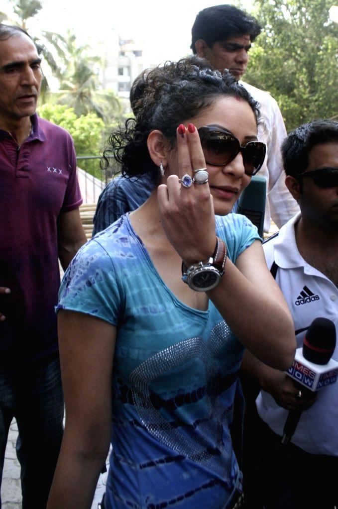 Actor Sanjay Dutt's wife Manyata Dutt shows her finger after casting her vote in Mumbai. - Sanjay Dutts