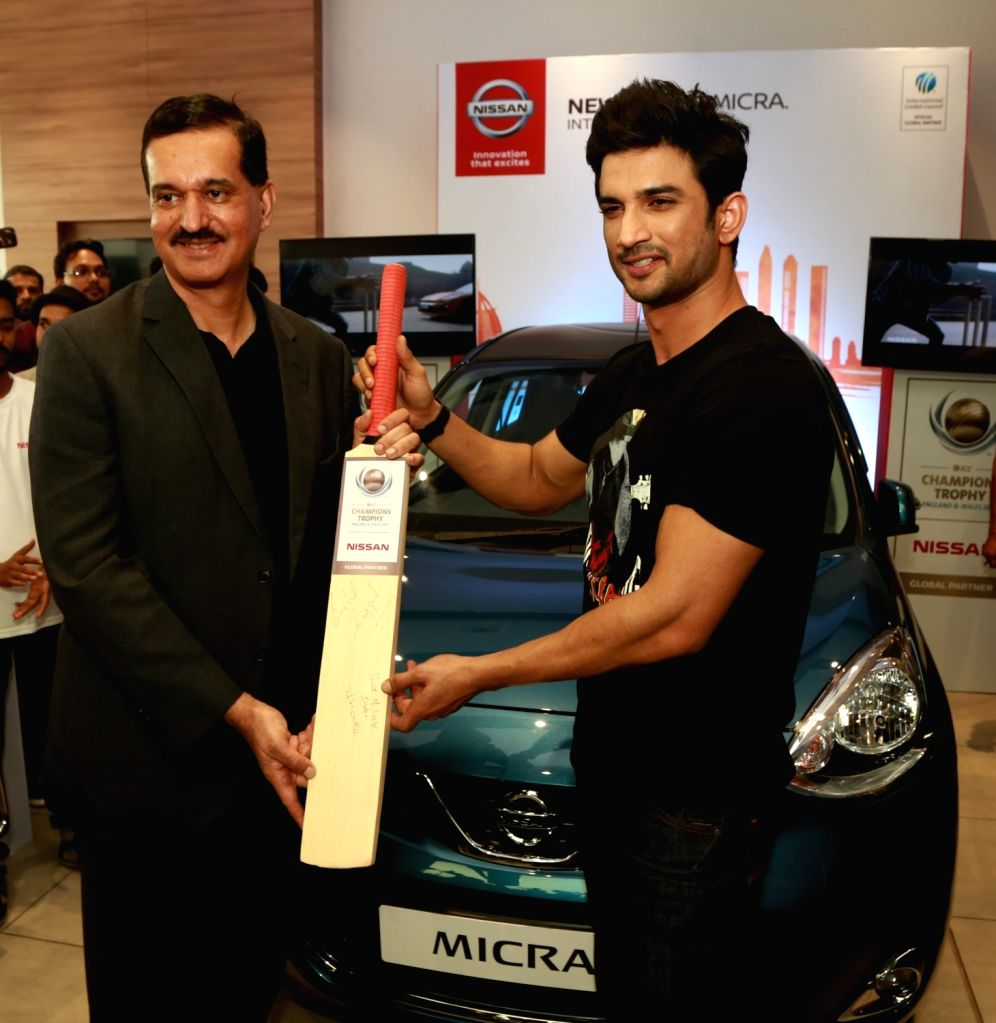 Actor Sushant Singh Rajput and Nissan Motor India MD Arun Malhotra sign a cricket bat to convey their best wishes to the Indian cricket team along with customers and fans during a special ... - Sushant Singh Rajput and Arun Malhotra
