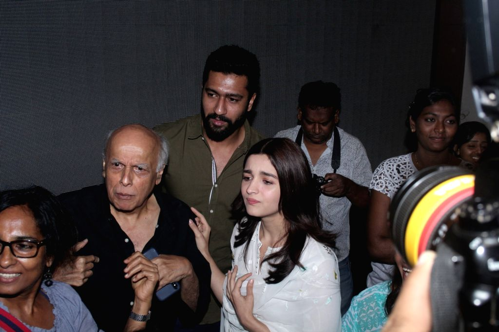 """Actors Alia Bhatt, Vicky Kaushal and filmmaker Mahesh Bhatt with crew members at the special screening of the film """"Raazi"""", in Mumbai on June 2, 2018. - Alia Bhatt and Vicky Kaushal"""