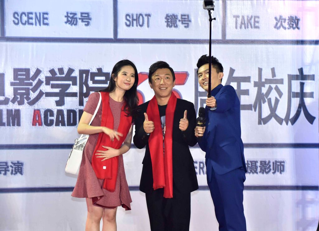 Actors Huang Bo(C) and Liu Yifei(L) take selfies during a celebration in Beijing Film Academy in Beijing, China, Oct. 17, 2015. Beijing Film Academy on Saturday ... - Huang B
