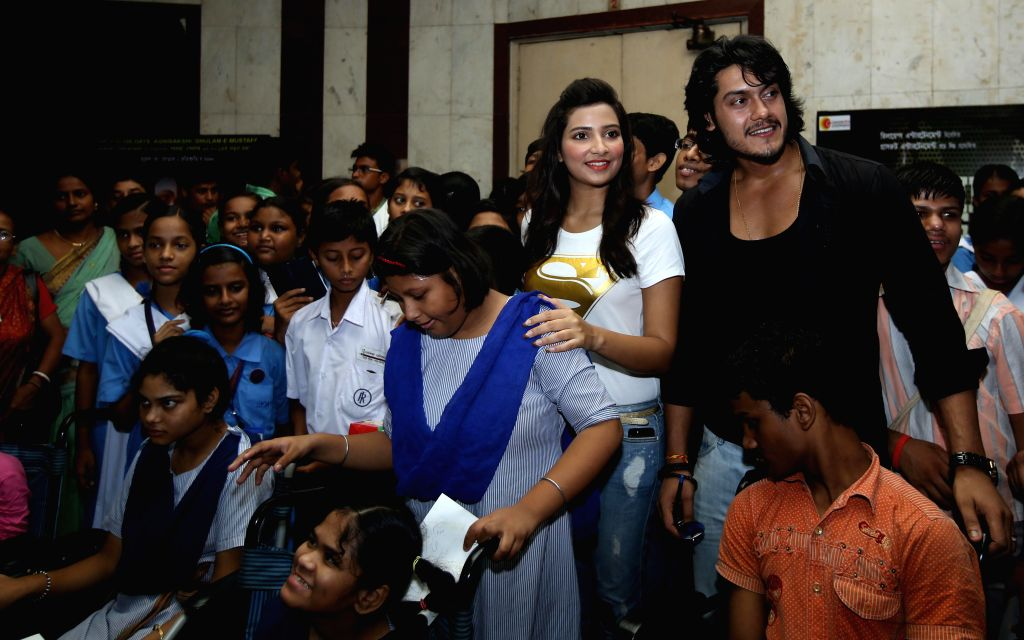 Actors Subhasree Ganguly and Sourav Chakraborty with children of Indian Institute of Cerebral Palsy during special screening of Bengali film 'GAME' at Bijoli Theatre in Kolkata on June 27, 2014. - Subhasree Ganguly and Sourav Chakraborty