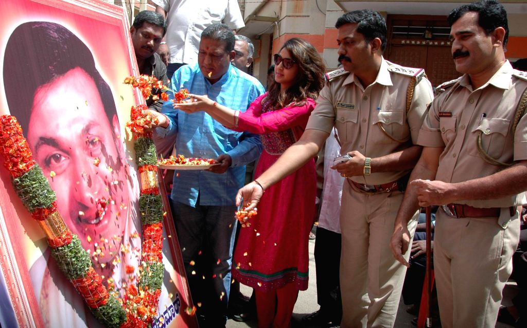 Actress Aindrita Ray and police personnel pay floral tribute to actor Dr. Rajkumar on the eve of his 85th birth anniversary in Bangalore on April 23, 2014.