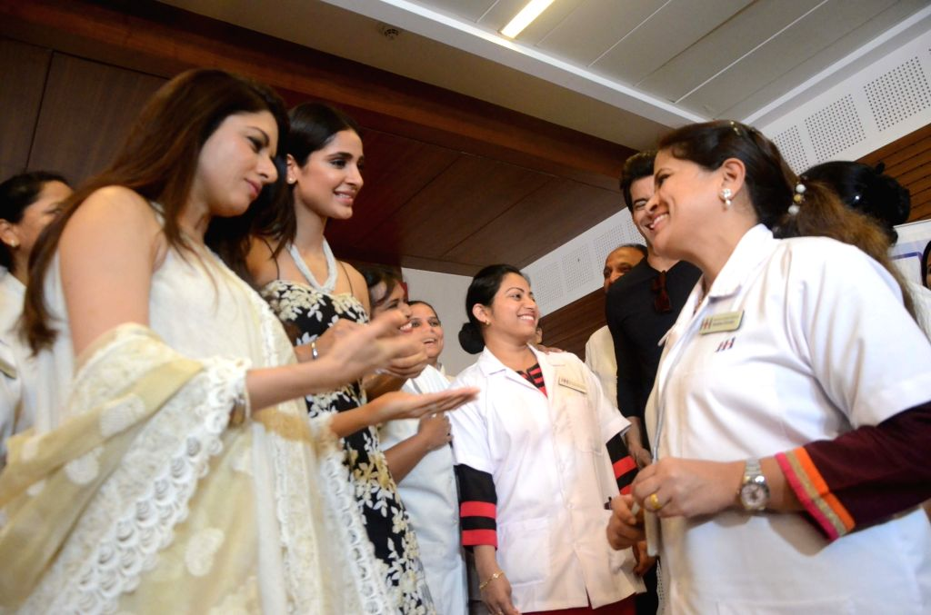 Actress Bhagyashree and Miss Diva Earth 2014 Alankrita Sahai interact with nurses as they celebrate International Women's Day with them at a healthcare centre in Mumbai on March 8, 2018. - Bhagyashree