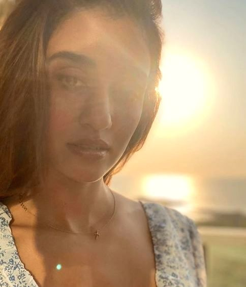 """Actress Disha Patani treated her fans with a stunning photograph of herself. Disha took to Instagram, where she shared a string of photographs. In one image, the """"Baaghi 2"""" star can be seen wearing a white floral summer dress.In the other photograph, - Disha Patani"""