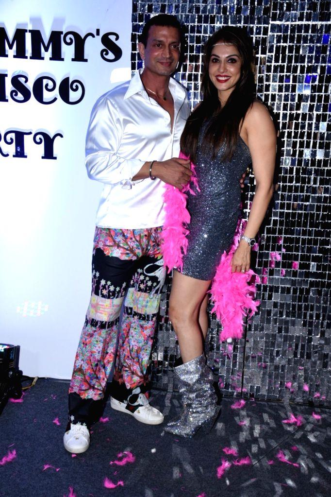 Actress Isha Koppikar with her husband Timmy Narang during her wedding anniversary party, in Mumbai on Dec 6, 2019. - Isha Koppikar