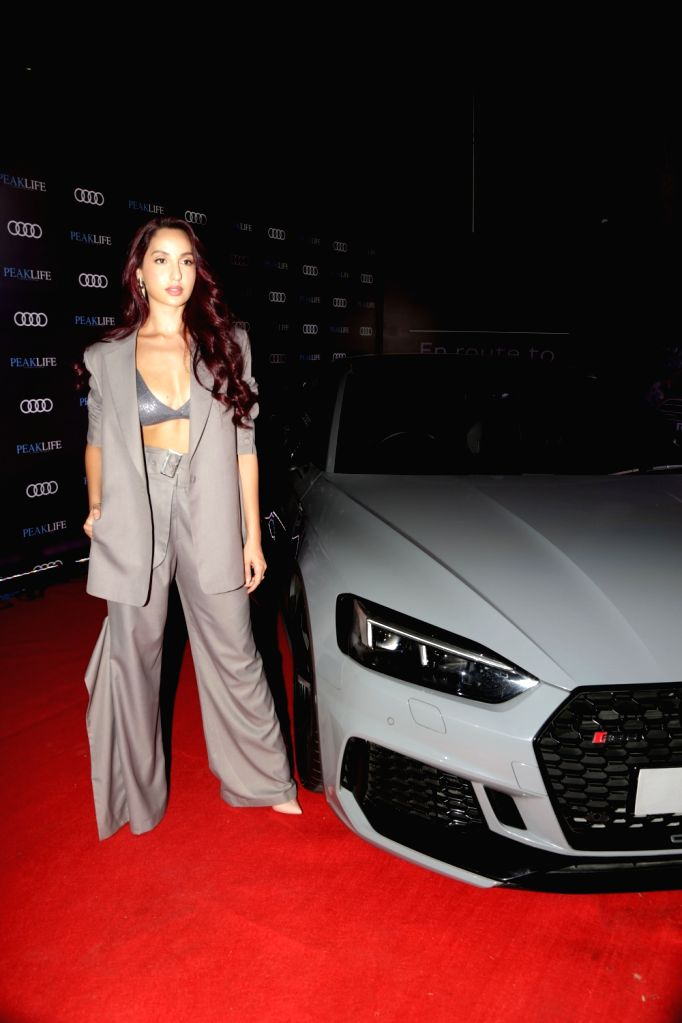 Actress Nora Fatehi poses with the Audi RS 5 Coupe at Audi Peaklife Fashion Capsule in New Delhi, on April 5, 2019. - Nora Fatehi