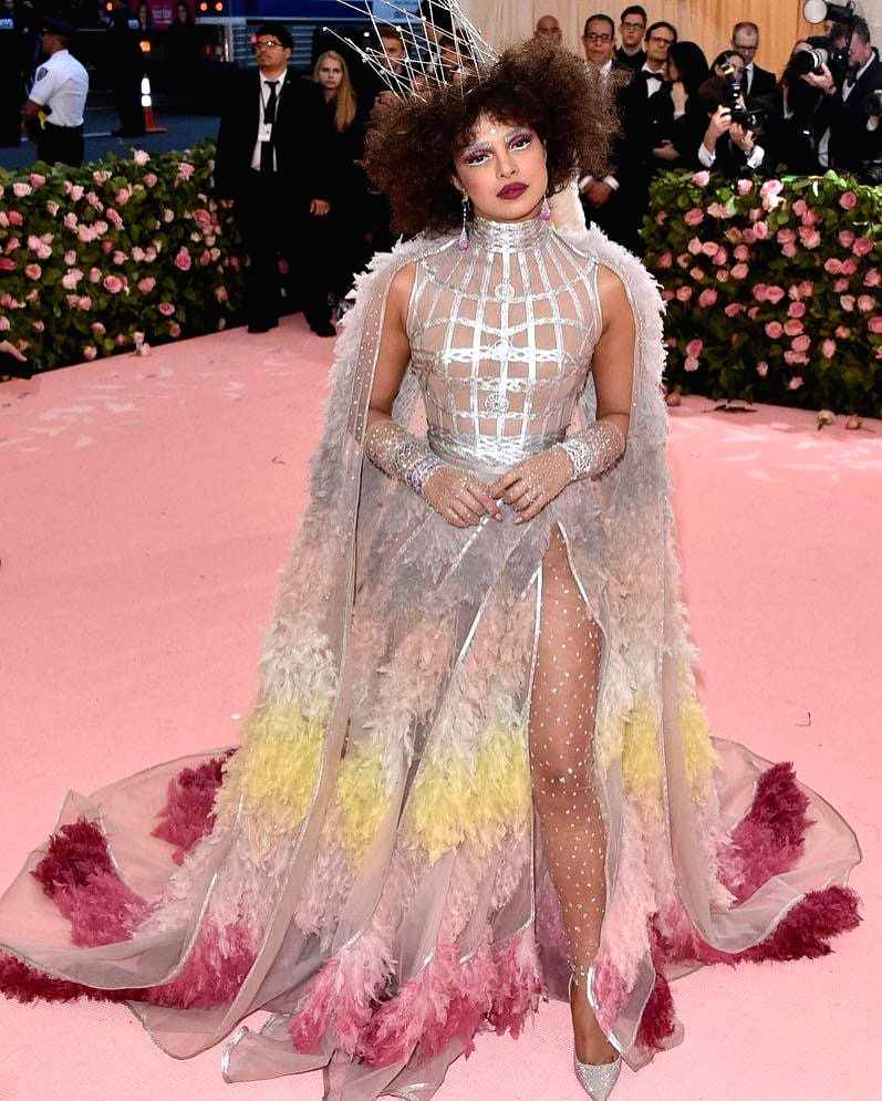 Actress Priyanka Chopra Jonas at the Met Gala 2019 in New York. For the event, the actress went bold and played up the theme with a zany look in a silver gown with colourful ruffled feathers, a very high leg split, a matching cape along with her big  - Priyanka Chopra Jonas