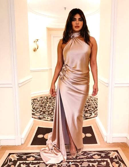 Actress Priyanka Chopra Jonas on Sunday shared her pre-Grammys' party look. Wearing a champagne  satin backless gown, Priyanka is definitely leaving her fans in awe of her fashion statement. - Priyanka Chopra Jonas