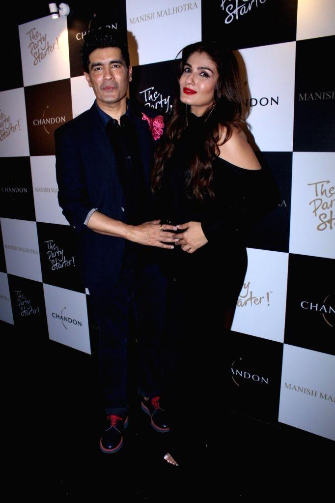 Actress Raveena Tandon and fashion Designer Manish Malhotra during the launch of Manish Malhotra X Chandon Champagne bottles Limited Edition End Of Year 2017 in Mumbai on Oct 9, 2017. - Raveena Tandon and Manish Malhotra