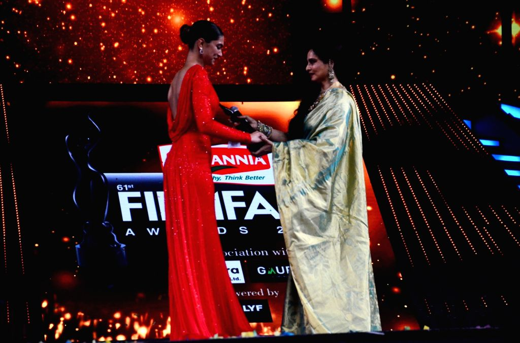 Actress Rekha presents the best actress award to Deepika Padukone performs during the 61st Britannia Filmfare Awards in Mumbai on January 15, 2016. - Rekha and Deepika Padukone