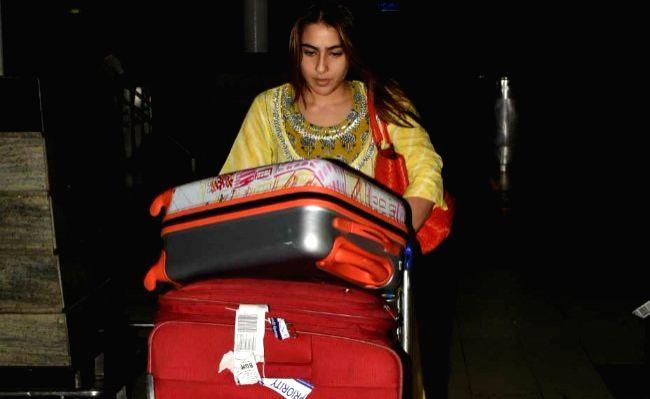 Actress Sara Ali Khan seen carrying her own luggage at Chhatrapati Shivaji International Airport in Mumbai. - Sara Ali Khan