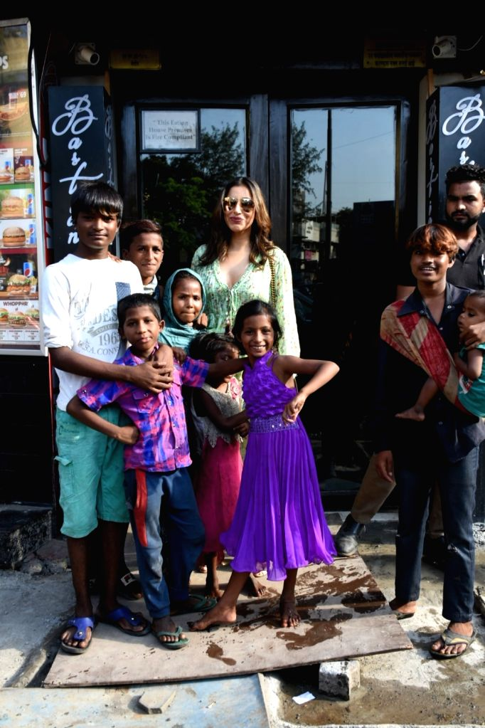 Actress Sophie Choudry poses for a photograph with children in Mumbai on May 13, 2019. - Sophie Choudry