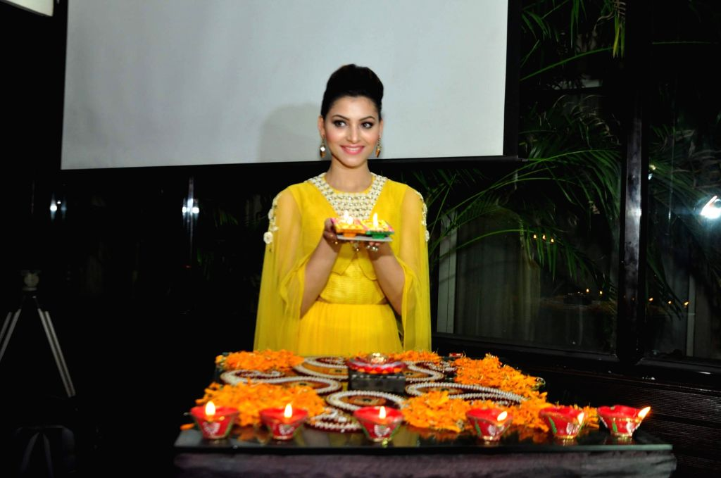 Actress Urvashi Rautela lights candles as she celebrates Diwali, The Hindu festival of lights in Mumbai on Oct 28, 2016. - Urvashi Rautela