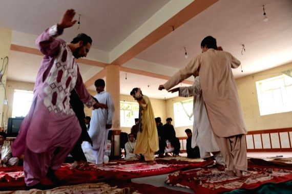 Addicts dance at Jaghara Treatment Center in Injil district of Herat province, western Afghanistan, April 15, 2021.