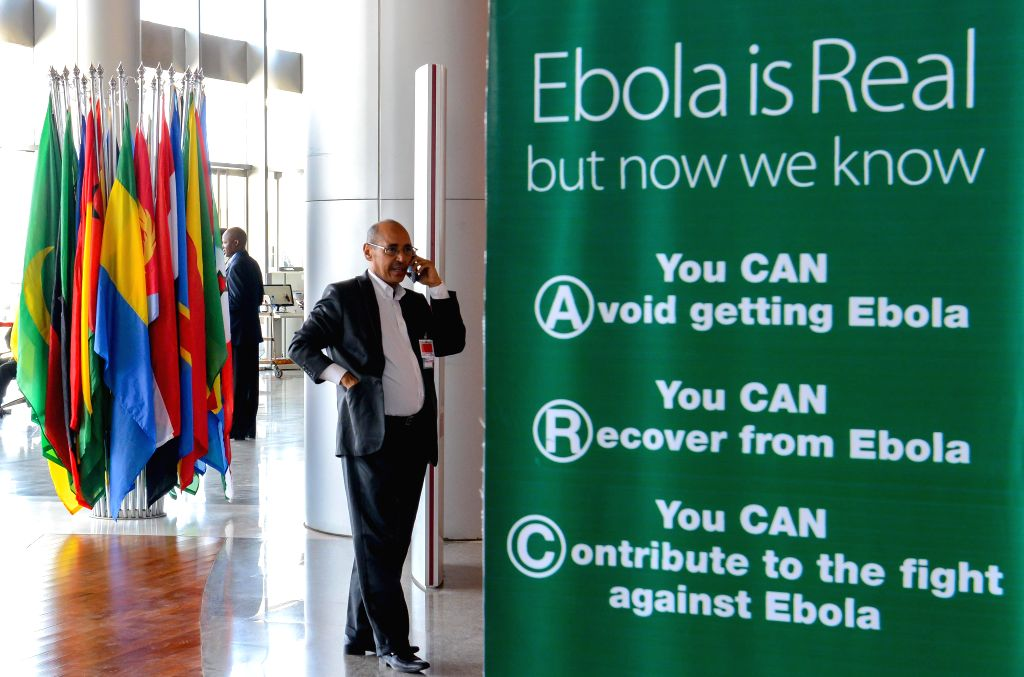 A man calls beside a poster with the theme of anti-Ebola Virus at the headquarters of African Union (AU) in Addis Ababa, Ethiopia, Jan. 27, 2014. The 22nd ...