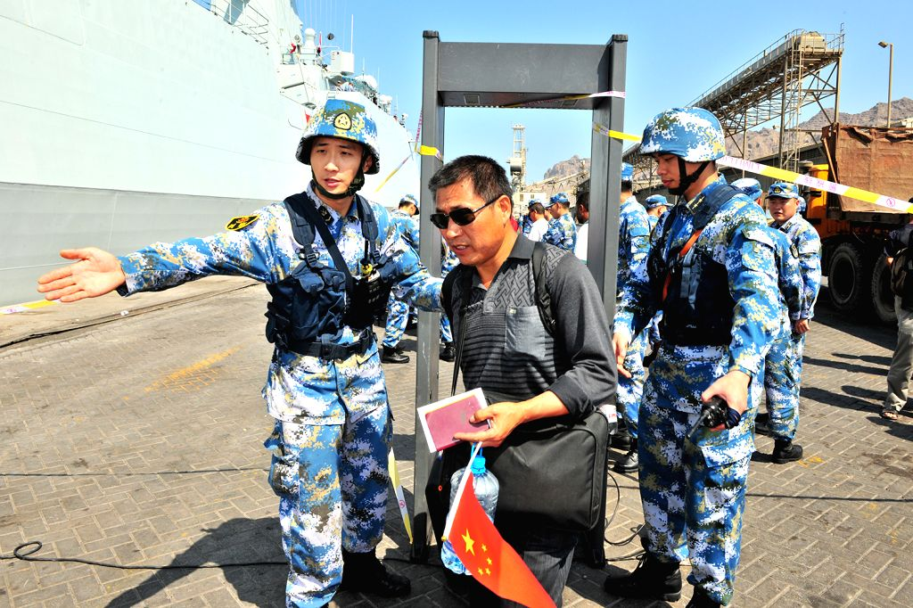 A Chinese citizen goes through security check before boarding a Chinese navy vessel in Aden Harbor, Yemen, March 29, 2015. China is withdrawing hundreds of ...