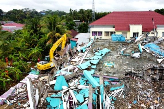 Aerial photo shows an excavator working on damaged buildings during a search operation after a 6.2-magnitude earthquake in Mamuju, West Sulawesi, Indonesia, Jan. 17, 2021.