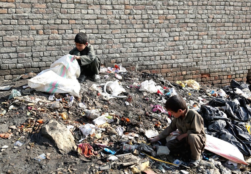 Afghan children collect scraps on the outskirts of Kabul city, capital of Afghanistan, Nov. 25, 2015. More than 11 million Afghan children, among which 40 percent are ...