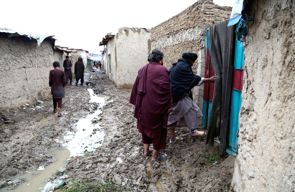 Afghan displaced people enter to a house at a makeshift camp in Kabul. (Xinhua/Sayed Momizadah/IANS)