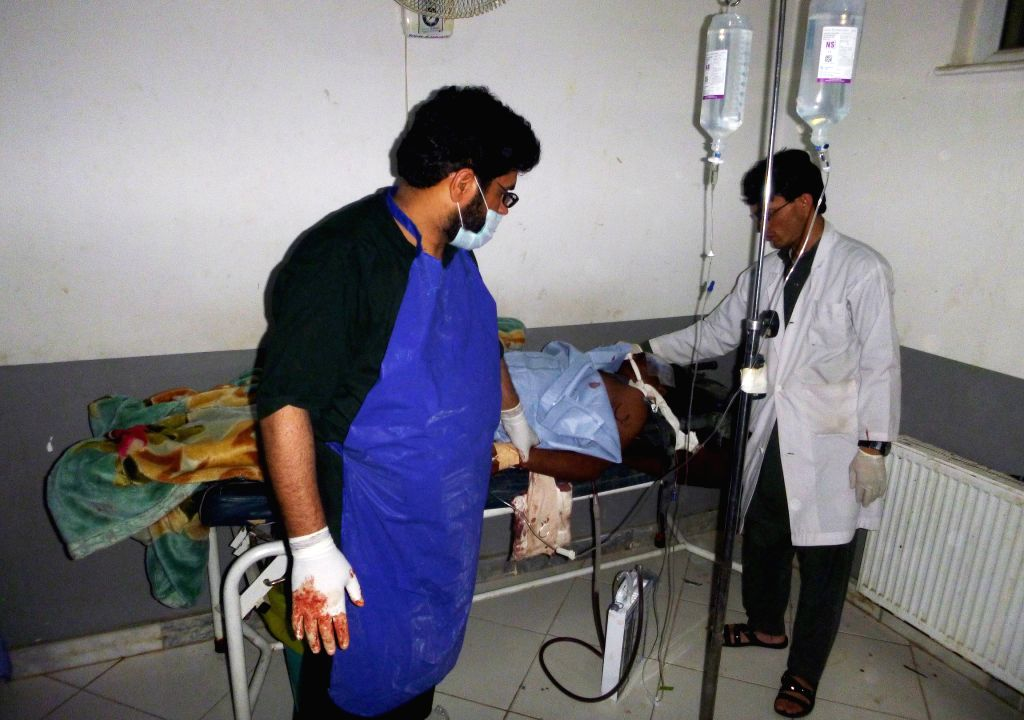 Afghan doctors treat a wounded man at a hospital following a suicide car bombing targeted foreign military base in Khost province, eastern Afghanistan, July 12, 2015. ...