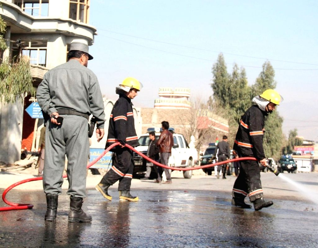 Afghan firefighters wash a road at the blast site in Nangarhar province, Afghanistan, Jan. 17, 2016. About 12 people were killed and 13 others wounded after a ...