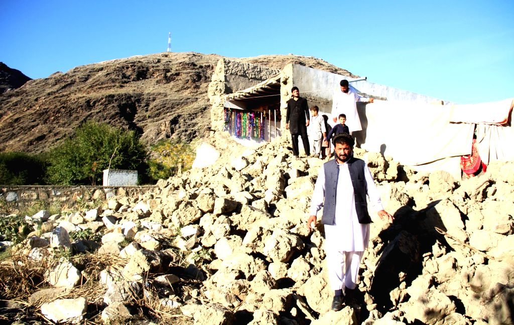 Afghan men and children stand on the debris of a destroyed house in Sawki district of eastern Kunar province, Afghanistan, on Oct. 28, 2015. The death toll in ...