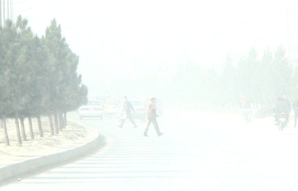 Afghan men walk in fog-shrouded street in Kabul, capital of Afghanistan, Nov. 19, 2015.